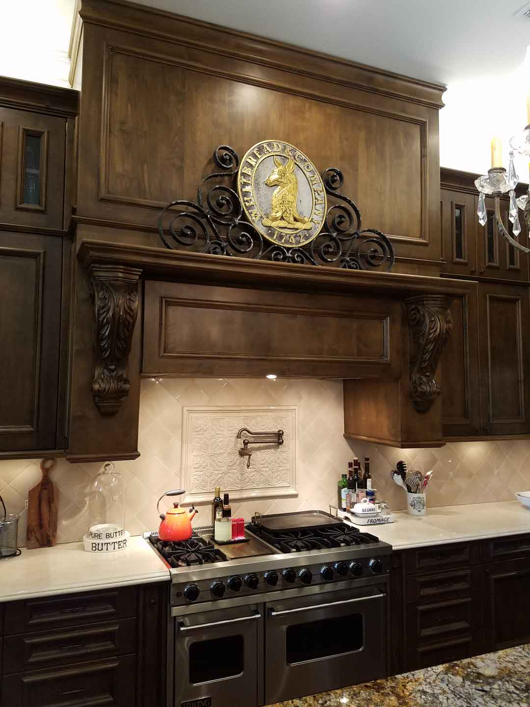 kitchen-gas-stove-with-pot-faucet-and-custom-hood-with-vintage-plaque-on-top