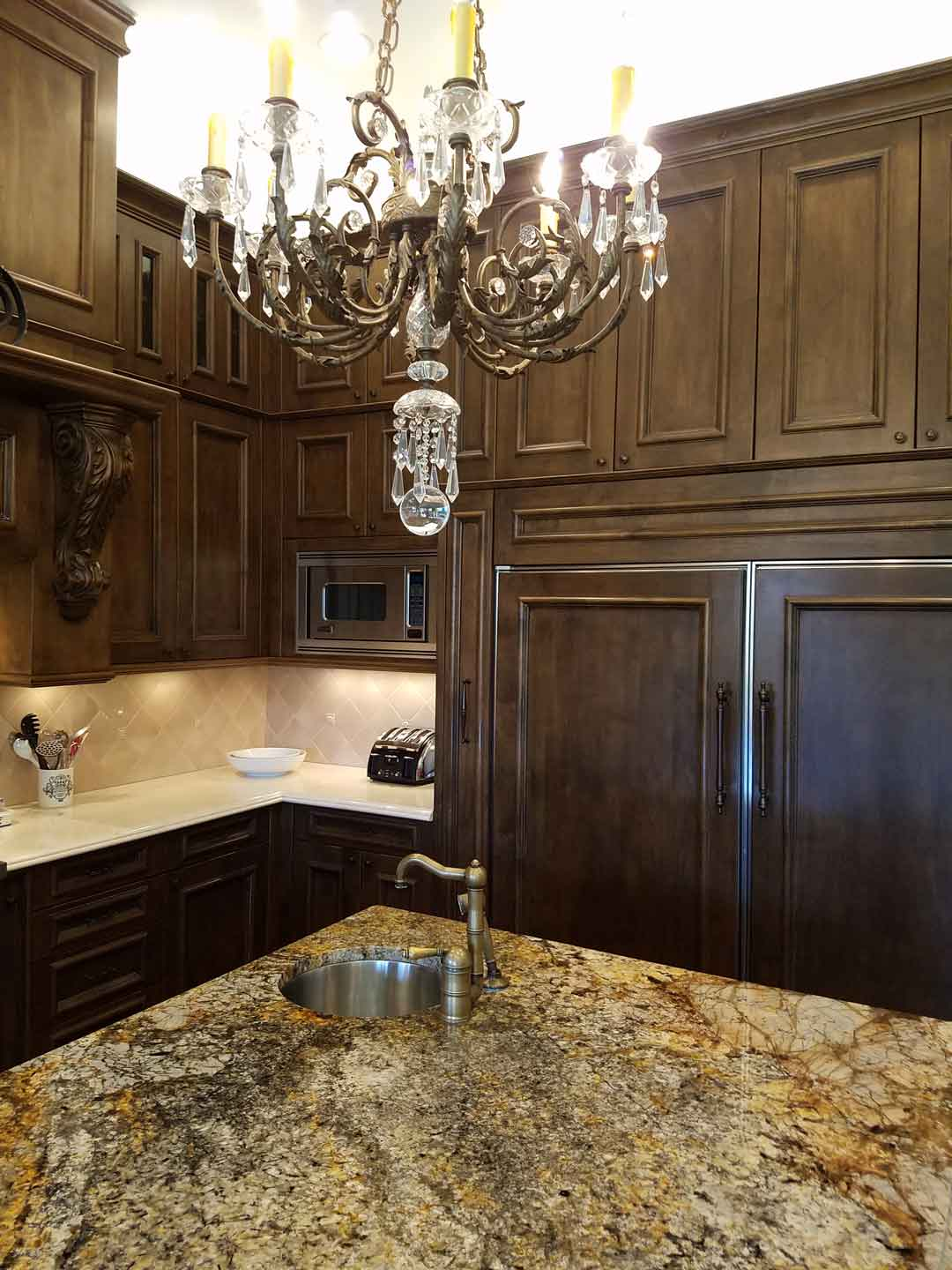 kitchen-island-granite-top-with-burnished-copper-faucet-and-custom-cabinetry-with-fly-flec